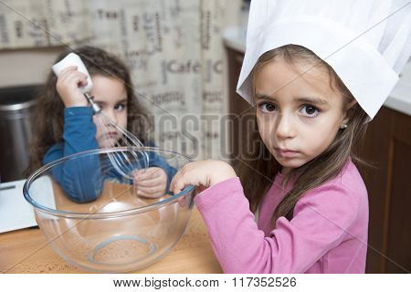 Portrait Of Cute Girl In Chef's Hat Looking At Camera