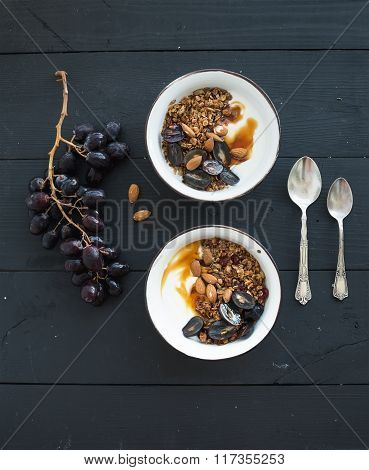 Healthy breakfast set. Bowls of oat granola with yogurt, fresh grapes, almond and  honey over black