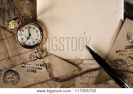 Vintage Pocket Clock And Pen On Old Letters Texture