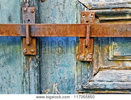 detail of an old wooden door with metallic rusty latch