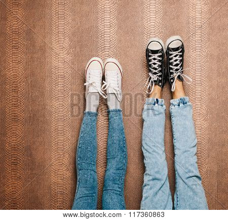 Young fashion couple's legs in jeans and sneakers feet up on the wall. Close up. Indoor. Warm color