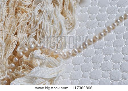photo of pearl string and threads on white textile textured background