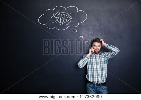 Irritated young man with beard solving a problem using mobile phone standing over blackboard background