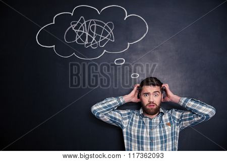 Confused bearded young man grabbing his head and thinking about problem with black board behind him