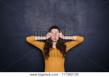 Young woman covering her eyes over black background