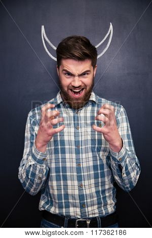 Shouting bearded young man playing role of devil standing over chalkboard background with drawn horns