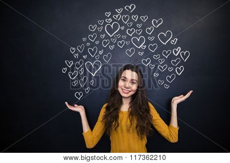 Beautiful smiling young woman holding drawing hearts on both palms over blackboard background
