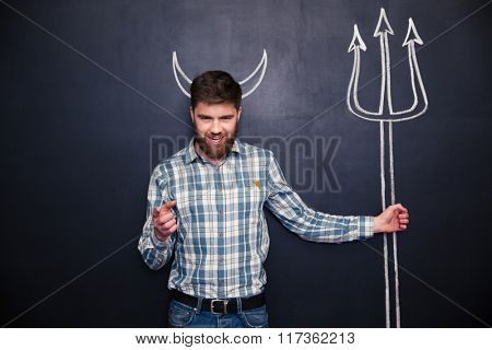 Attractive young man with devils horns holding trident and pointing on you over blackboard background