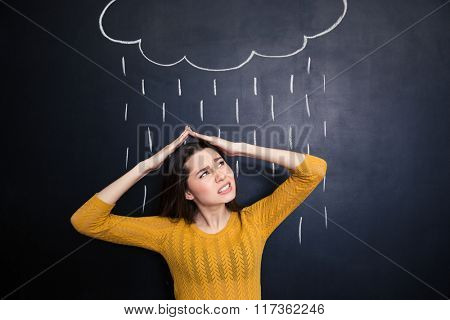 Annoyed young woman covering her head with hands from rain drawn on background of chalkboard