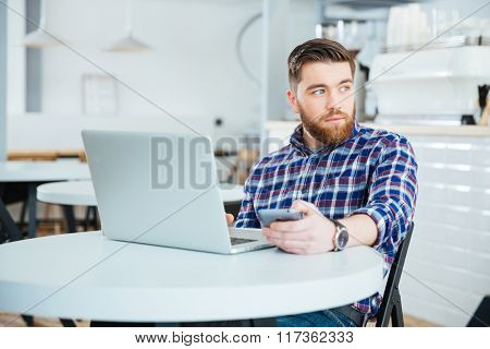 Pensive casual man sitting at the table with laptop computer in cafe