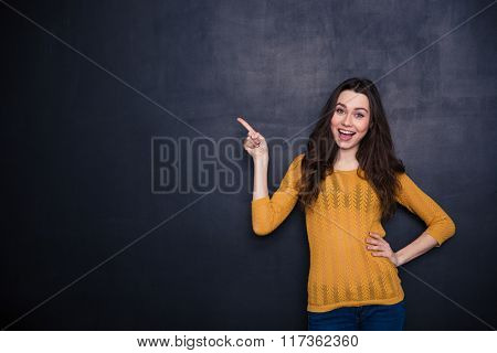 Cheerful casual woman pointing away over black background