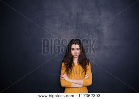 Sad woman standing with arms folded over black background and looking at camera