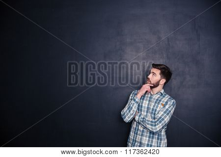 Portrait of a thoughtful man looking up at copyspace over black background