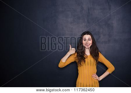 Smiling casual woman showing thumb up over black background