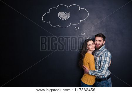 Smiling beautiful loving young couple standing and hugging  over background of chalkboard