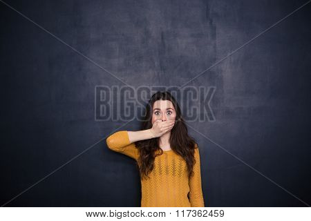 Young woman covering her mouth over black background