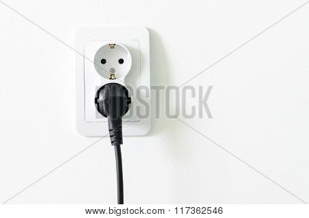 European White Electrical Outlet Socket And Black Cable Pluged In On White Wall