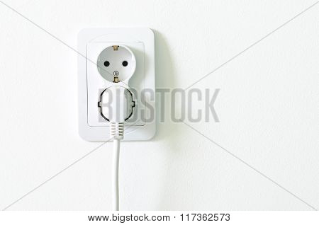 European White Electrical Outlet Socket Pluged In On White Wall