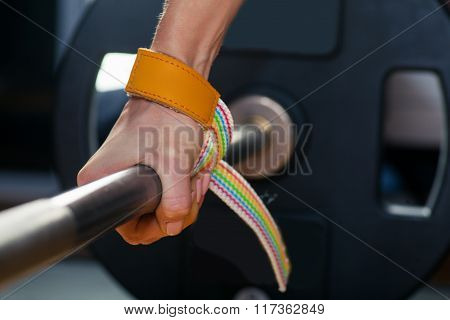 Hand on the barbell. Young athlete getting ready for weight lifting training carpal bandage