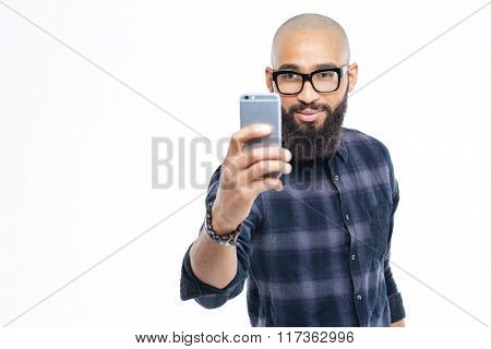 Handsome young hairless african young man with beard taking selfie using smartphone