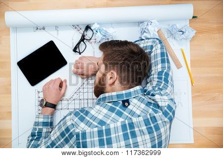 Top view of exhausted bearded young architect sleeping on workplace