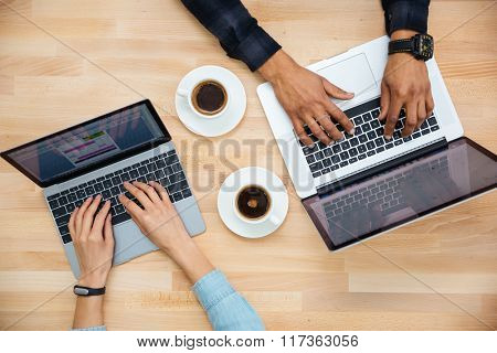 Top view of hands of african man and caucasian woman typing on two laptops and drinking coffee on wooden table