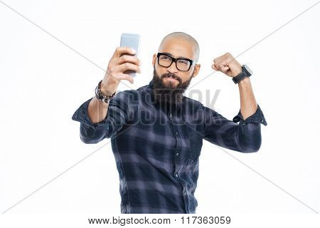 Handsome hairless african american man with beard showing biceps and making selfie