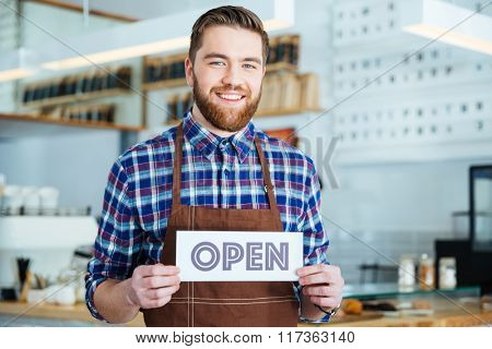 Happy attractive young barista in plaid shirt and brown apron holding open sign at the coffee shop
