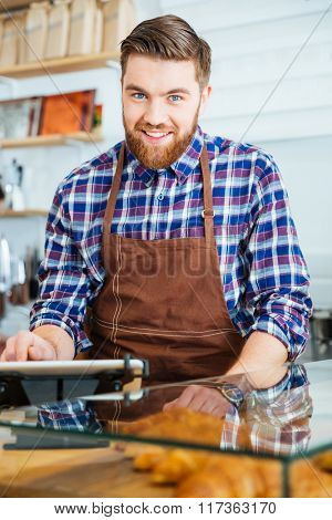 Portrait of attractive happy bearded barista in brown apron at work in coffe shop