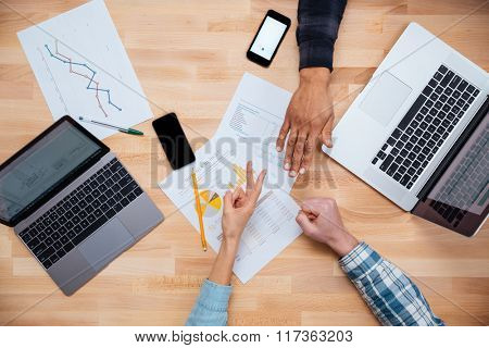 Multiethnic group of young people woking for monthly budget with laptops and gesturing rock paper scissors game