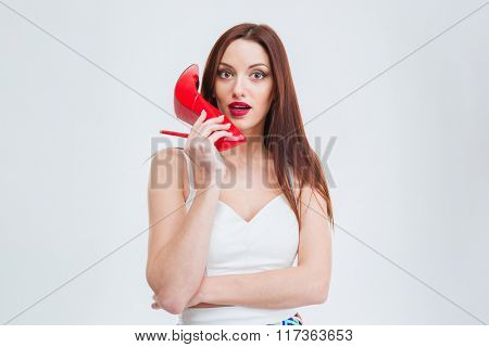 Young beautiful woman holding red heel isolated on a white background