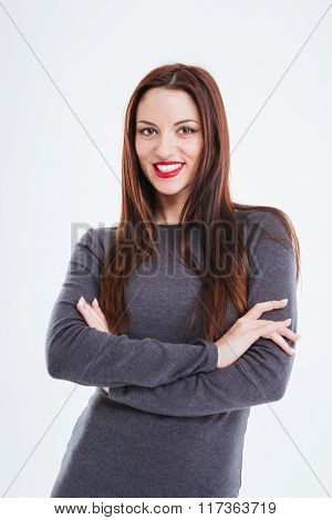 Portrait of happy beautiful young woman with red lips standing with arms crossed over white background