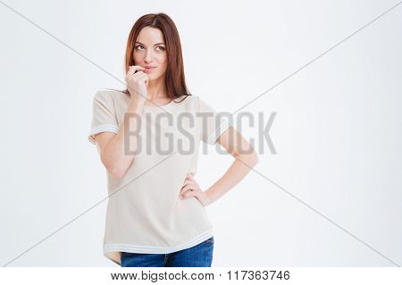 Thoughtful young woman standing and thinking over white background