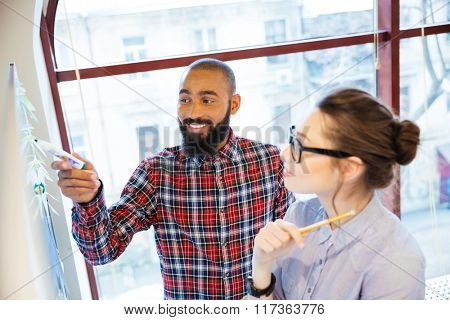 Pretty young woman in glasses and bearded african american man standing near whiteboard and preparing for presentation