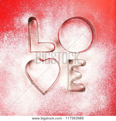 Love shaped cookie cutters and flour on red background