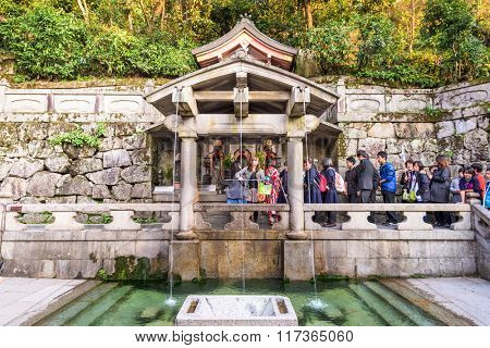 KYOTO, JAPAN - NOVEMBER 30, 2015: Visitors que for the Otowasan waterfalls of Kiyomizudera Shrine. The falls are traditionally believed to have wish granting powers.