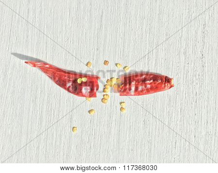 A dry red chilly broken into two pieces with its seeds visible.