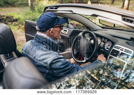 Rear View Of Senior Man In Sports Car In Nature.