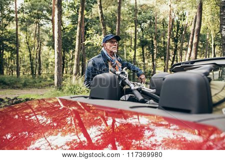 Senior Man Standing Next To Cabriolet With Bicycle On Back Seat.