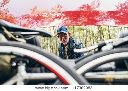 Active Senior Man At Trunk Of Car. Going For A Bicycle Tour.
