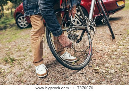 Hands Of Senior Man Mounting Chain Of Bicycle.