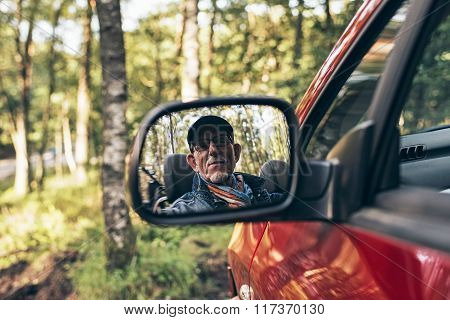 Senior Man Looking In Mirror Of Car.