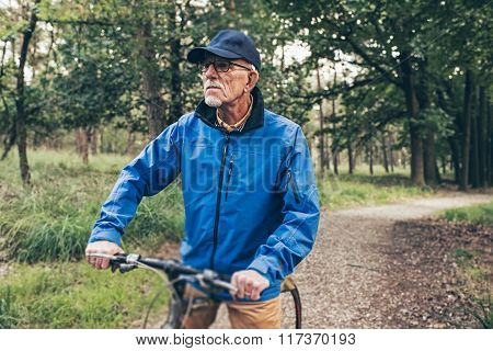 Resting Senior Man Standing With Bicycle On Forest Trail.