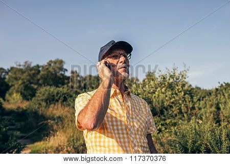 Senior Man Calling With Cellphone Outdoors In Nature.