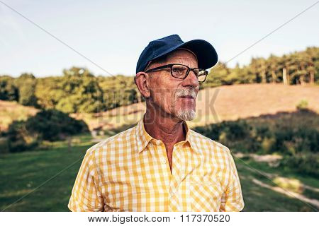 Senior Man With Beard And Cap Outdoors In Park.