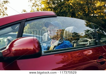 Side View Of Senior Man Sitting In Sports Car Outdoors In Park.