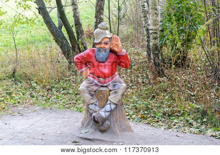 Sculpture Of An Old Man Sitting On A Stump In A Forest In The National Park
