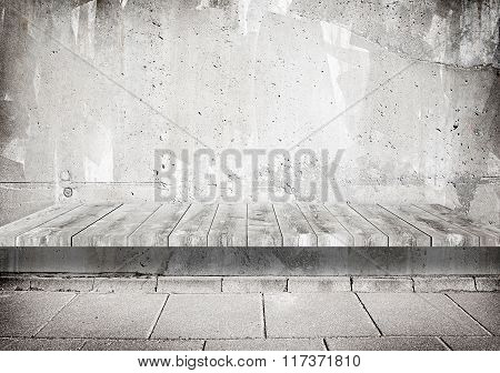 Concrete grunge weathered gray wall with wooden shelf, table surface and tile walkway