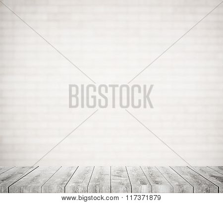 Blurred white brick wall with gray wooden shelf, walkway or table surface