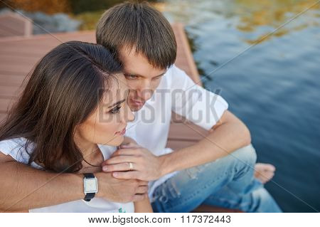 Couple Embracing On A Wooden Pier Near The River